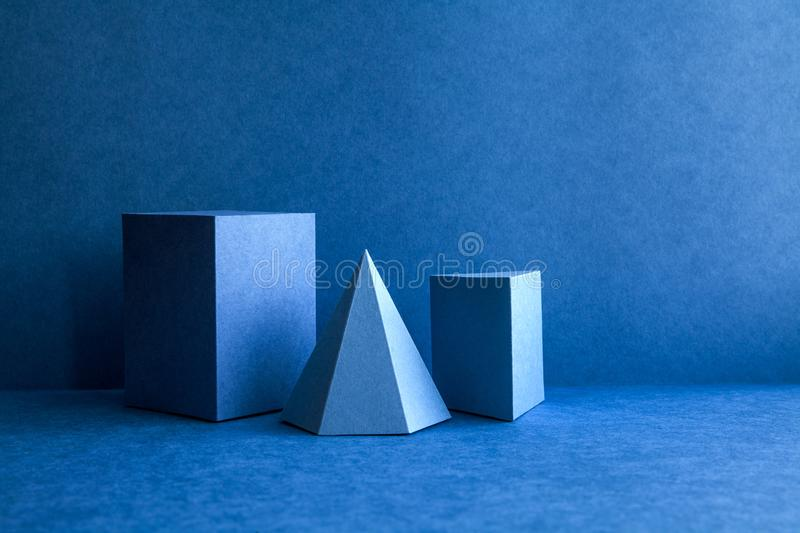 Geometrical figures still life composition. Three-dimensional prism pyramid tetrahedron rectangular cube objects on blue. Background. Platonic solids figures stock images