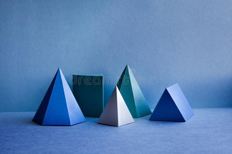 Geometrical figures still life composition. Three-dimensional prism pyramid tetrahedron rectangular objects on blue. Background. Platonic solids figures royalty free stock photo