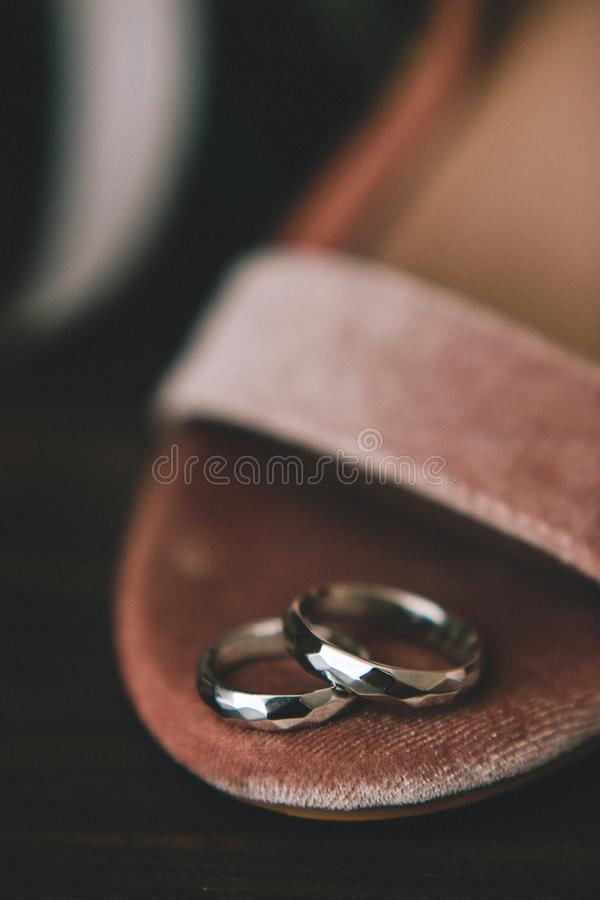 Geometrical original wedding rings from gold on the bride`s shoes from pink velvet. Close-up royalty free stock photos
