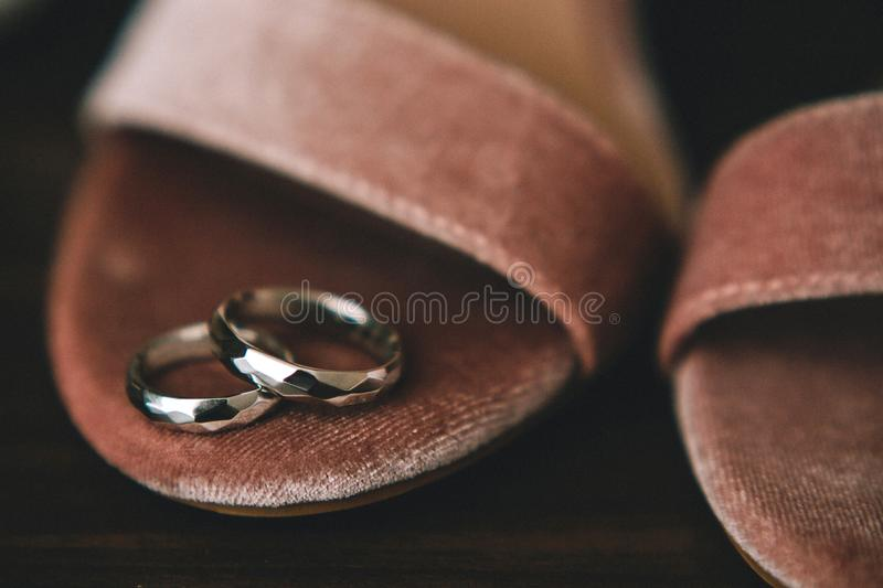 Geometrical original wedding rings from gold on the bride`s shoes from pink velvet. Close-up royalty free stock photography