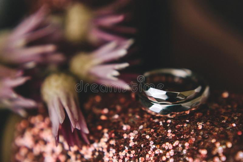 Geometrical original wedding rings of gold on shiny sparkling pink shoes beside flowers. Close-up stock photo