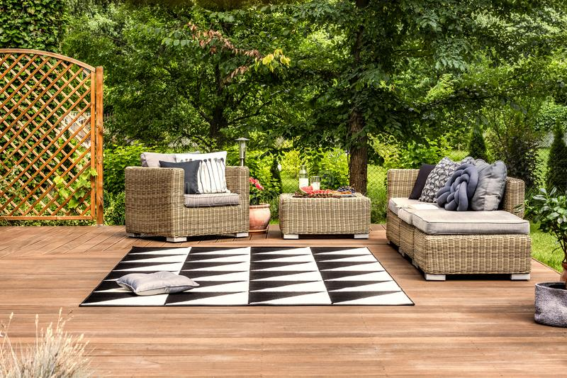 Geometrical rug and rattan furniture set on a terrace in a garden full of trees stock images