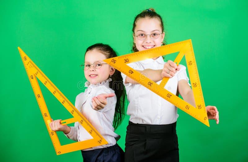 Geometrielieblingsthema Bildung und Schulkonzept Sch?ler, die Geometrie lernen Kinderschuluniformgrün stockfoto