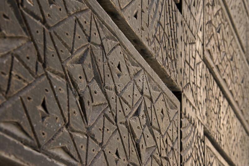 Geometrisch geschnitzte Holztüren - geschossen über Türoberfläche mit kurzem DOF stockfotografie