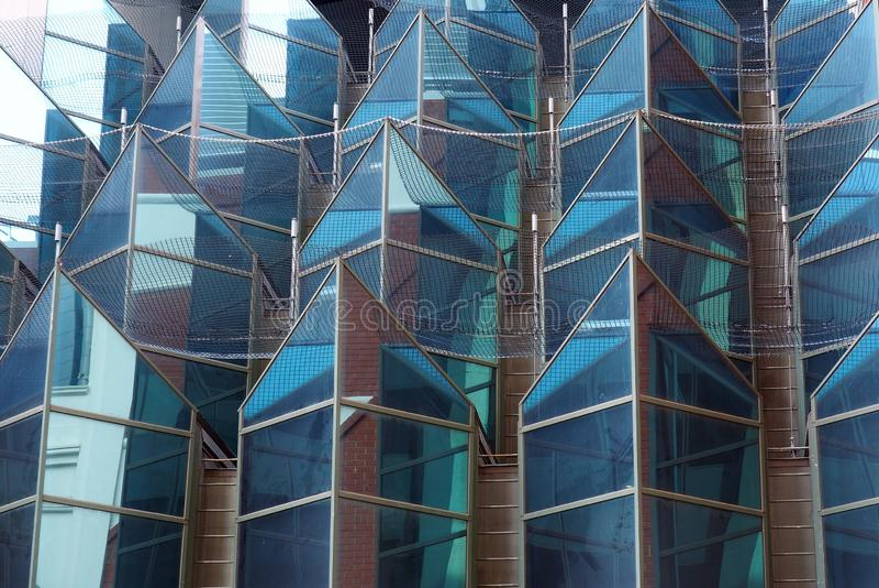 Geometrische geformte Glasfassade auf modernem hohem Aufstiegs-Gebäude lizenzfreie stockfotografie