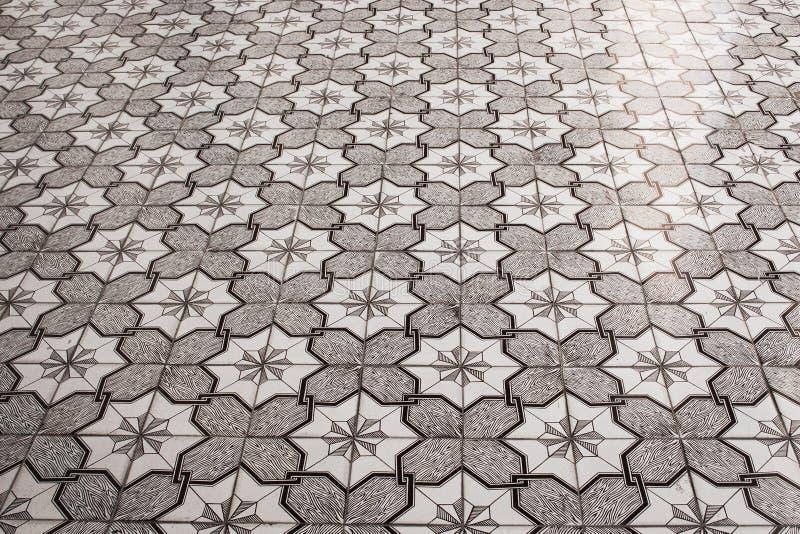 Geometrisches Muster auf dem Schwarzweiss-Parkettboden acht-spitze Sterne, Quadrate, Kreuze und Linien graue Beschaffenheit, Hint stockbild