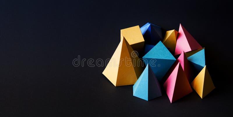 Geometriska fasta diagram för färgrikt minimalistic sammansättningsabstrakt begrepp på svart texturerad pappers- bakgrund Pyramid royaltyfri fotografi