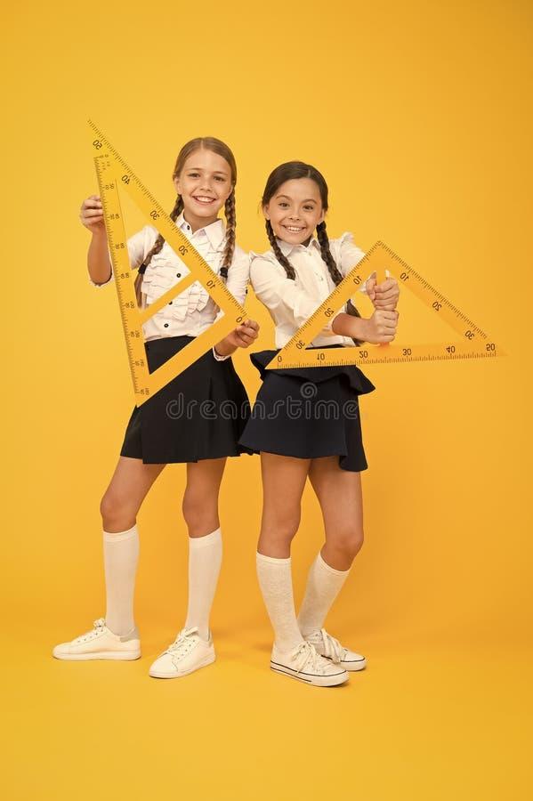 Geometriska former Elever använder logglinjal stamdiscipliner tillbaka till skolan Math och geometri Ungar i uniform vid gult royaltyfri foto