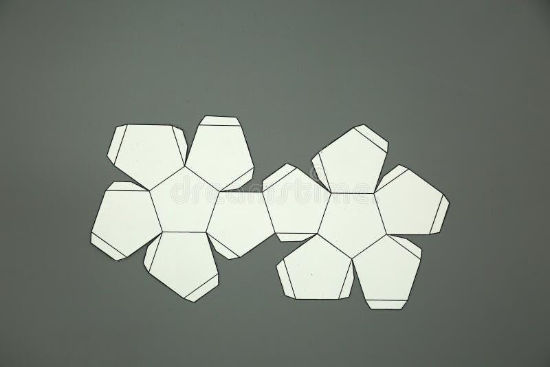 Geometriskt formsnitt ut ur papper och som fotograferar på grå bakgrund dodecahedron 2d hopfällbara form att bilda en form 3d ell arkivbild