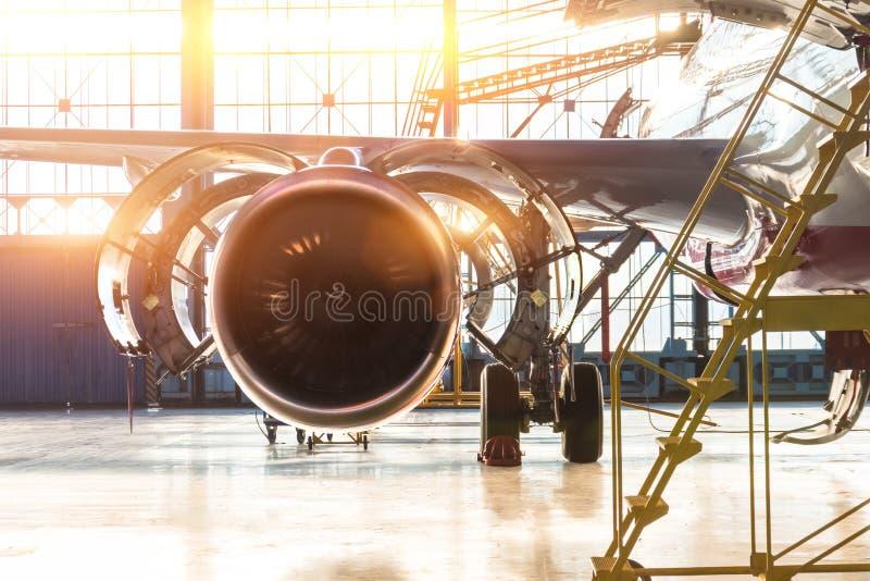 Geopend de motor straalonderhoud van het kapvliegtuig in de hangaartreden, met heldere lichte gloed bij de poort stock foto