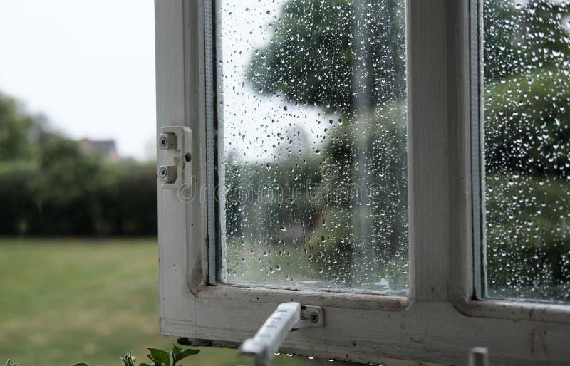 Geopend houten ontworpen venster die waterdruppeltjes op het glas tonen stock fotografie