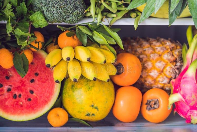Geopend ijskasthoogtepunt van vegetarisch gezond voedsel, trillende kleurengroenten en vruchten binnen op koelkast Veganistkoelka stock foto's