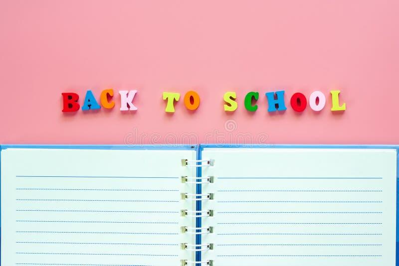 Geopend leeg notitieboekje met houten teksten TERUG NAAR SCHOOL op roze bedelaars stock foto