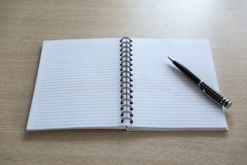 Geopend notitieboekje met een strook en met een handvat op de lente op een lichte houten lijst stock foto's
