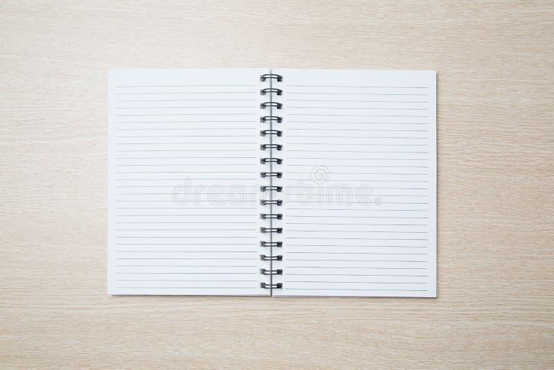 Geopend notitieboekje met een strook op de lente op een lichte houten lijst in centrum Te schrijven plaats stock foto