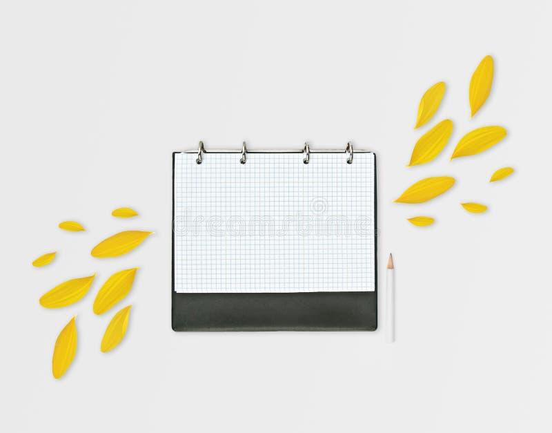 Geopende dagontwerper met geel bloemblaadjes en potlood, op grijze achtergrond Vlak leg Werkruimte met geruit blad, plaats voor t stock fotografie