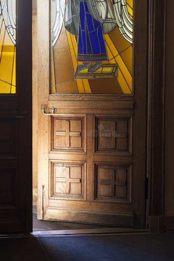 Geopende deur voor kerk met hoek op gebrandschilderd glasvenster royalty-vrije stock fotografie