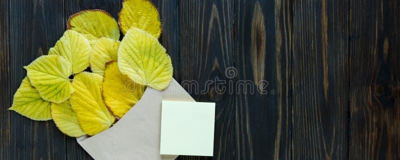 Geopende document envelop op oude bruine houten achtergrond met gele bladeren Uitstekende stijl van mededeling royalty-vrije stock foto's