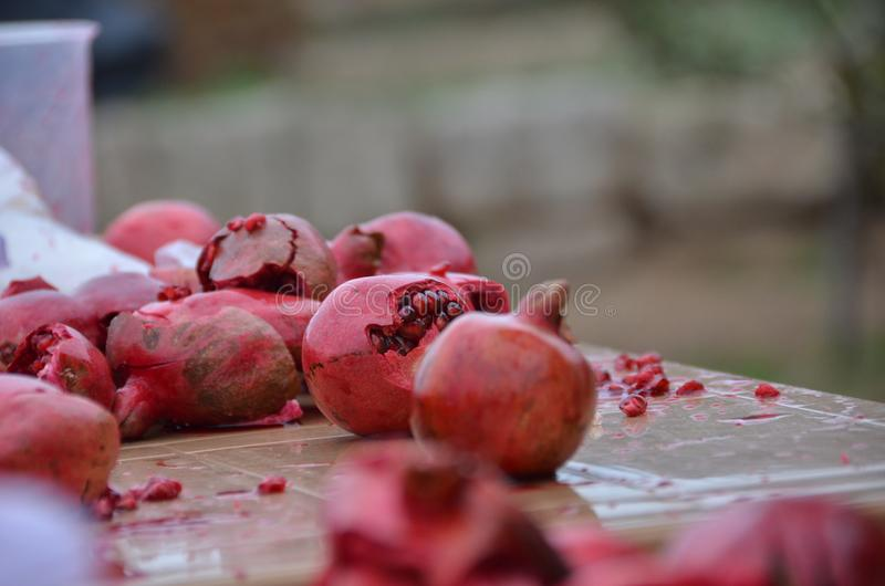 Geopende granaatappels Verpletterde granaatappels samengeperste granaatappel granaatappel op aardachtergrond die wordt geïsoleerd stock afbeelding
