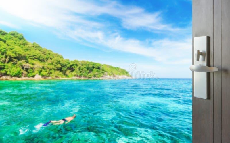 Geopende houten deur voor toerist het snorkelen in tropische duidelijke overzees dichtbij het groene eiland stock foto
