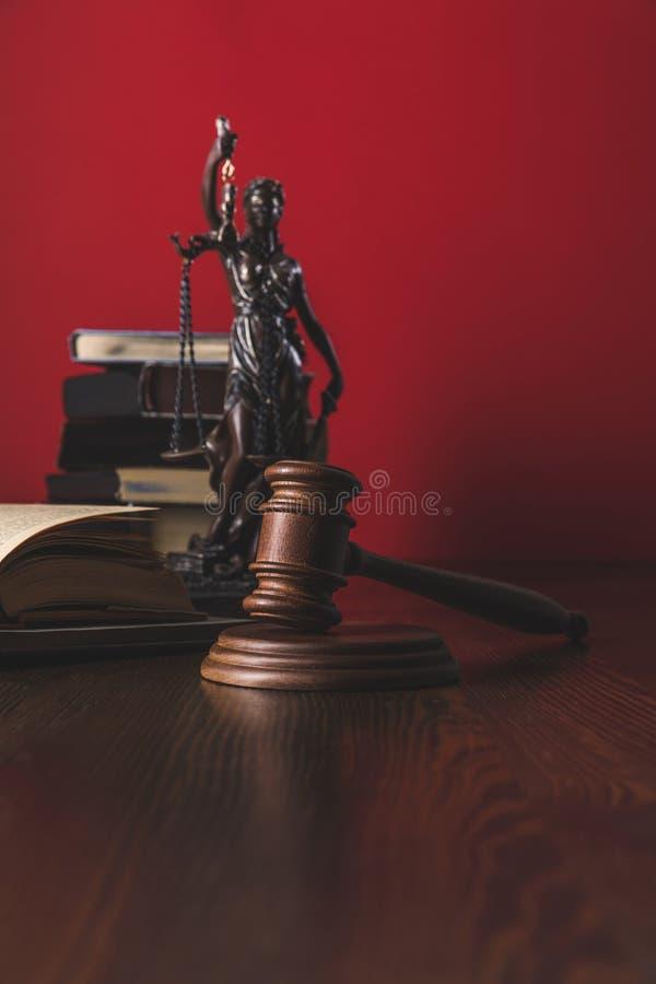 geopende juridische boeken met het standbeeld en de hamer van de damerechtvaardigheid op houten lijst, stock foto