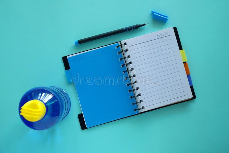 Geopende laptop met pen en waterfles op blauwe achtergrond royalty-vrije stock afbeelding