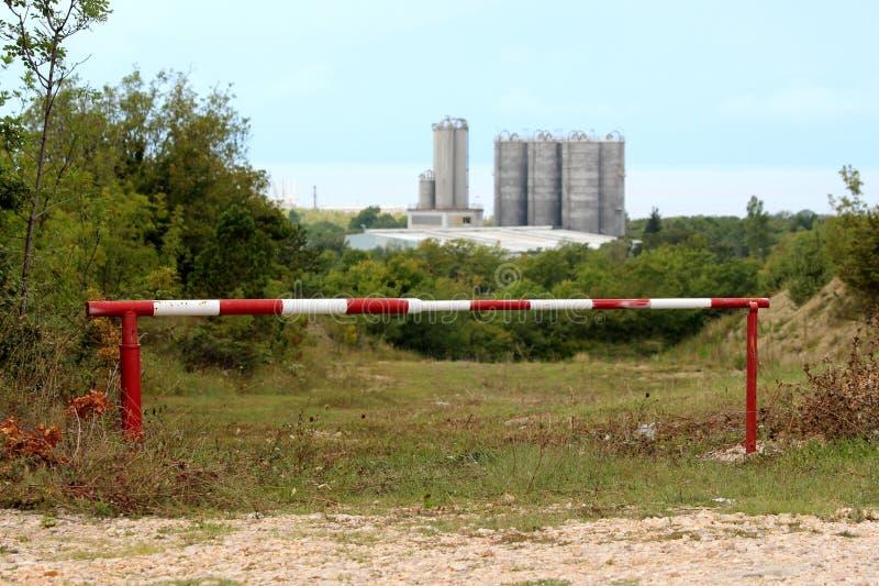 Geopende metaal rode en witte helling die toegang tot weg verhinderen die naar grote industriële complex met lange concrete opsla stock foto's