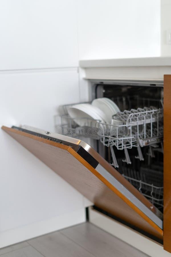 Geopende moderne afwasmachinemachine met platen en koppen op keuken stock afbeeldingen