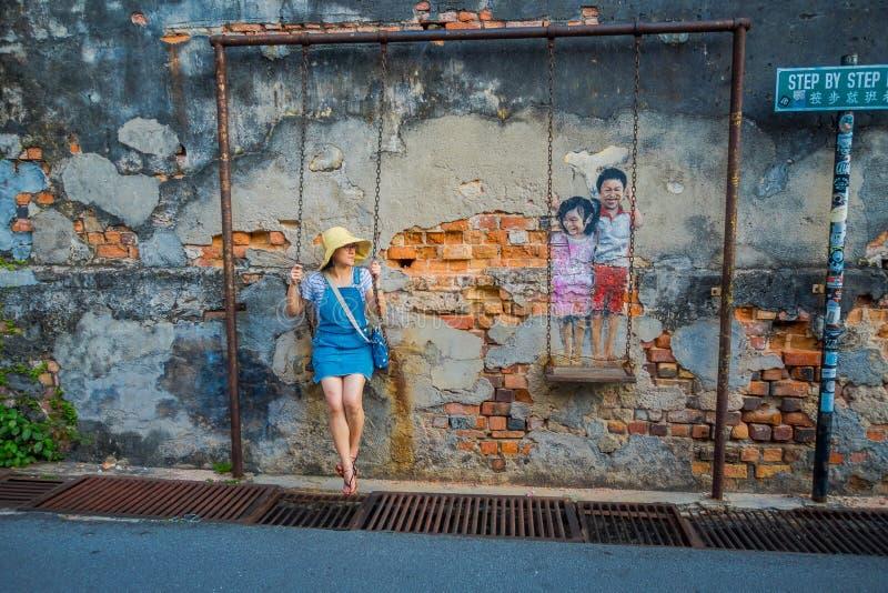 George Town, Maleisië - Maart 10, 2017: Onbekende vrouwentoerist en de Kinderen op het de straatart. van de Schommelingsmuurschil stock afbeelding