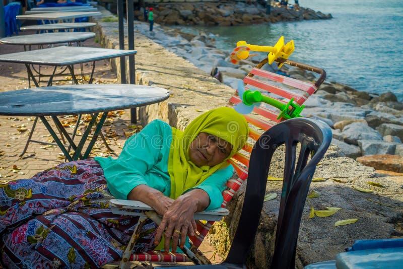 George Town, Maleisië - Maart 10, 2017: Sluit omhoog mening van niet geïdentificeerde oude vrouw die een dutje in de promenade va royalty-vrije stock afbeeldingen