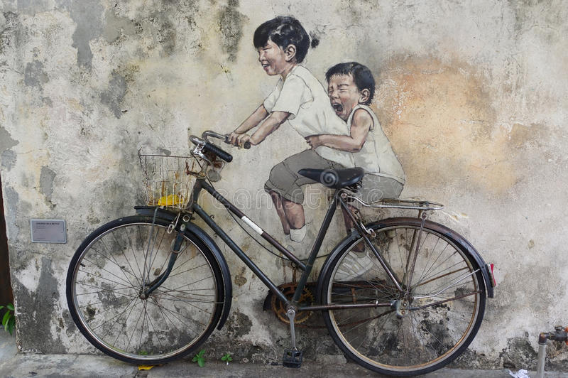 George Town, Penang, Malaysia - April 18, 2016: Little Children. On a Bicycle street art mural by Lithuanian artist Ernest Zacharevic in Georgetown, Penang in stock photography