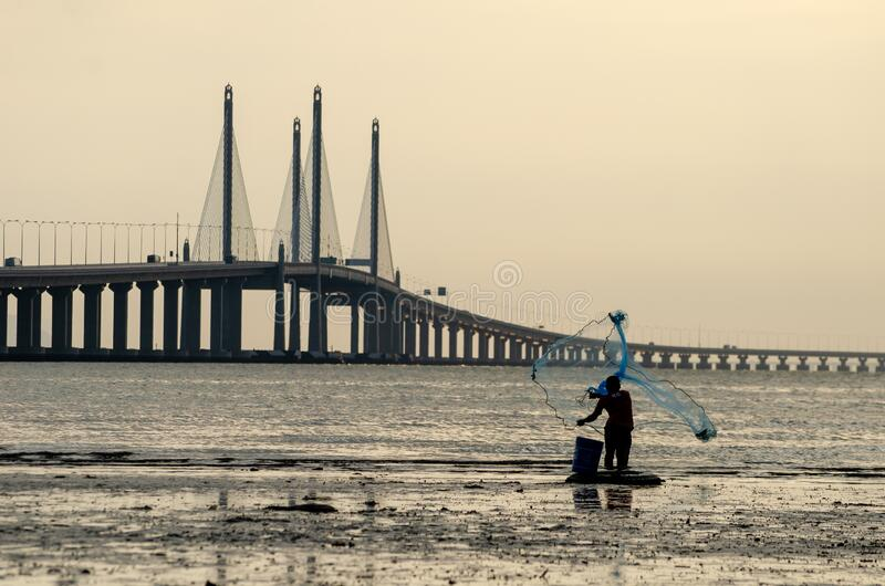 Fisherman cast net. Background is Penang Second Bridge. George Town, Penang/Malaysia - Dec 28 2019: Fisherman cast net. Background is Penang Second Bridge royalty free stock photography