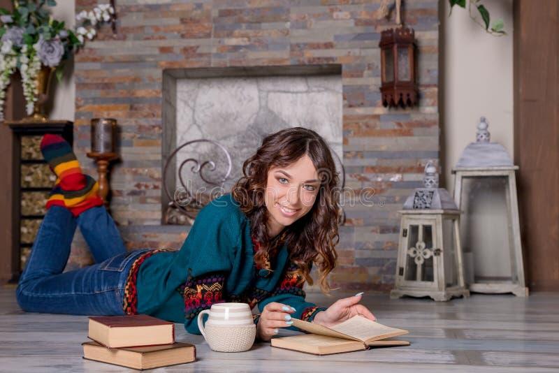 georgeous典雅的深色的妇女看书画象在舒适壁炉附近的 内部射击 读教育 免版税库存图片