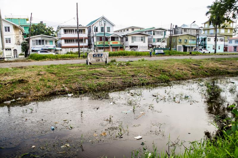 Street and a canal in Georgetown. GEORGETOWN, GUYANA - AUGUST 10, 2015: View of a street and a canal in Georgetown, capital of Guyana stock images