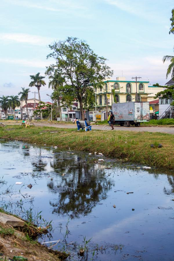Street and a canal in Georgetown. GEORGETOWN, GUYANA - AUGUST 10, 2015: View of a street and a canal in Georgetown, capital of Guyana royalty free stock image