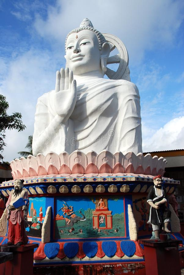 Georgetown, Malaysia: Giant White Buddha. A giant white Buddha seated on a colourful base with bas relief panels overlooks a courtyard at the Thai Wat (Temple) stock photography