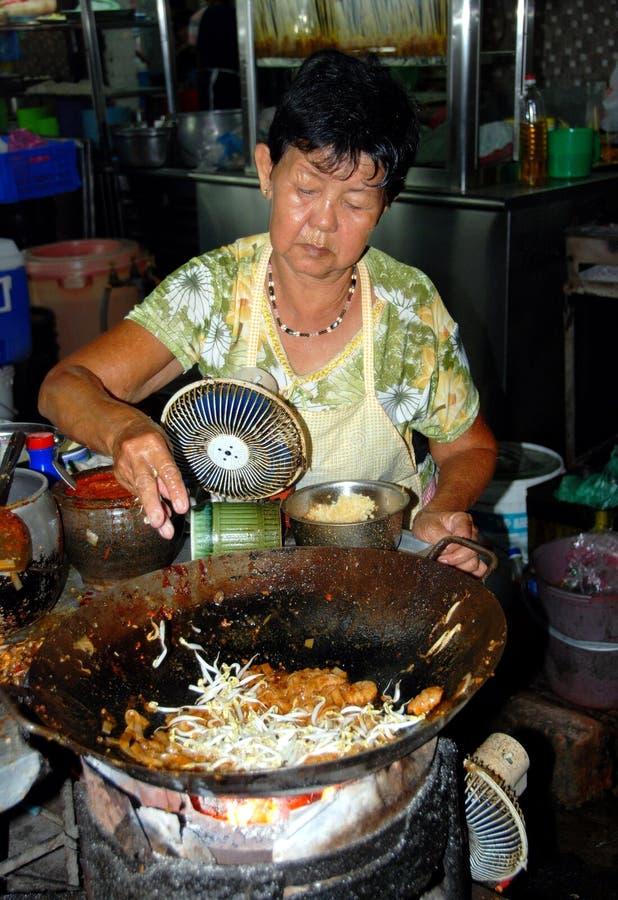 Georgetown, Malesia: Donna che cucina con il Wok fotografia stock