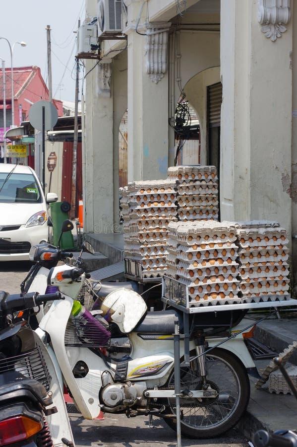 GEORGETOWN, PENANG, MALASIA - 18 de abril de 2016: Porción de huevo del pollo embalada en un cliente que espera de la vespa para  imagenes de archivo