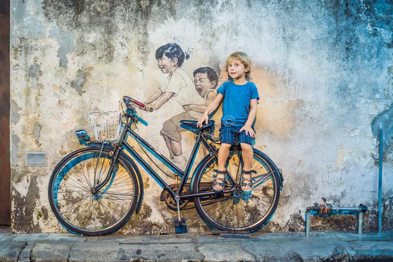Georgetown, Penang, Malaysia - April 20, 2018: Boy on a bicycle. Public street art Name Children on a bicycle painted 3D. On the wall that`s two little Chinese stock photography