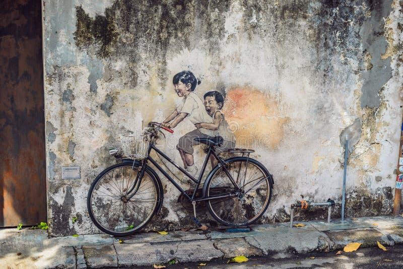 Georgetown Penang, Malaysia - April 20, 2018: Målade kända barn för offentlig gatakonst på en cykel 3D på väggen som ` s två tänd fotografering för bildbyråer