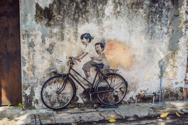 Georgetown, Penang, Malaysia - April 20, 2018: Public street art Name Children on a bicycle painted 3D on the wall that. `s two little Chinese girls riding stock photos