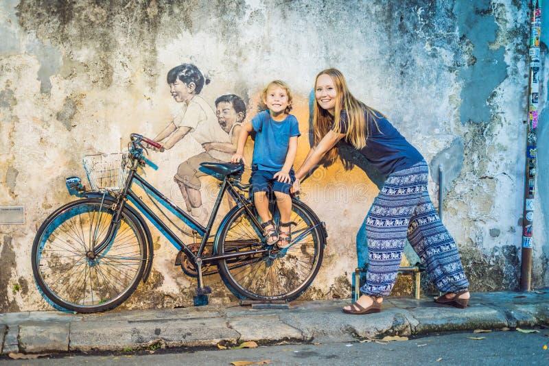 Georgetown, Penang, Malesia - 20 aprile 2018: Madre e figlio su una bicicletta Bambini di nome pubblici di arte della via su una  immagini stock libere da diritti