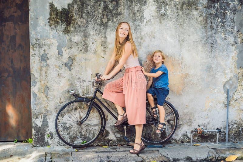 Georgetown, Penang, Malesia - 20 aprile 2018: Madre e figlio su una bicicletta I bambini di nome pubblici di arte della via su un fotografia stock libera da diritti