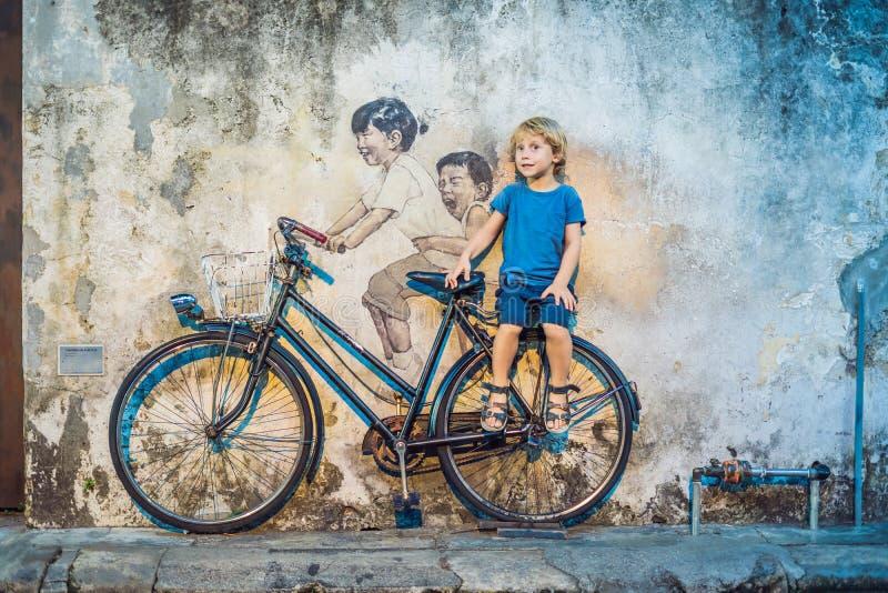 Georgetown, Penang, Malesia - 20 aprile 2018: Ragazzo su una bicicletta I bambini di nome pubblici di arte della via su una bicic fotografia stock