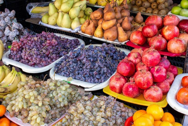 Georgia den lokala basaren Sale av nationella sötsaker från druvor och muttrar - 'Churchkhela ', nya och torkad frukter och gröns royaltyfri foto