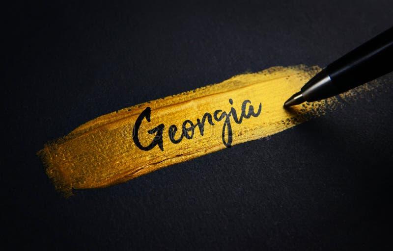 Georgia Handwriting Text no curso dourado da escova de pintura imagens de stock