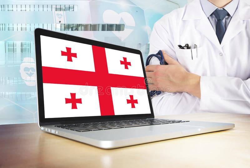 Georgia healthcare system in tech theme. Georgian flag on computer screen. Doctor standing with stethoscope in hospital. Cryptocurrency and Blockchain concept royalty free stock photo