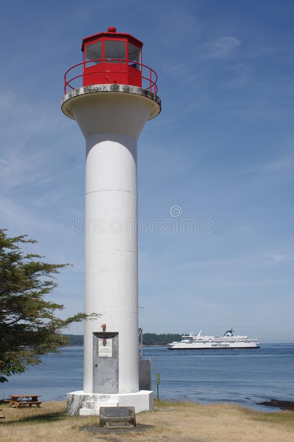 Lighthouse with passing ferry in the background. Georgia Point lighthouse on Mayne island  with BC Ferries, car and passenger ferry, in the background royalty free stock images
