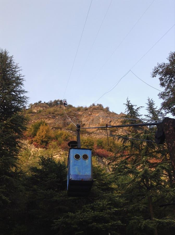 Georgia stad Chiatura, den gamla blåa kabelbilen för kabelbil på bakgrunden av berg royaltyfria foton