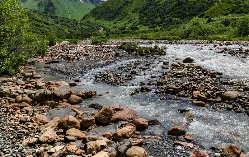 Georgia, Svaneti, Trek from Ushguli to Shkhara glacier. Mountain river with amazing red stones and a stream of water royalty free stock photos